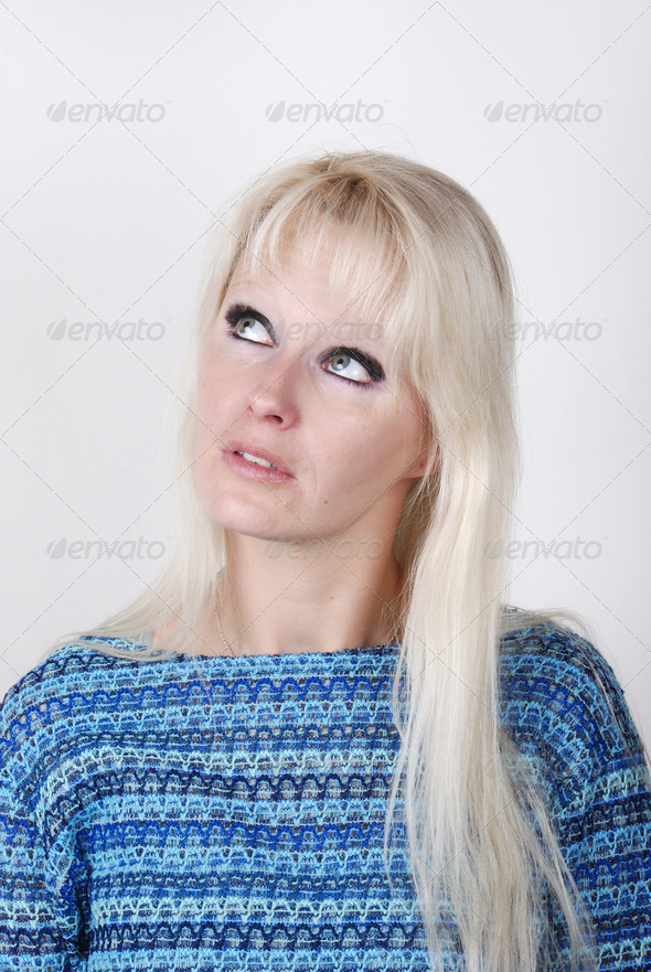 Portrait of young blond woman thinking and looking somewhere up - Stock Photo - Images