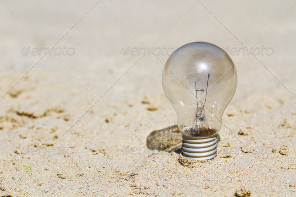 electric lamp bulb on sand - Stock Photo - Images