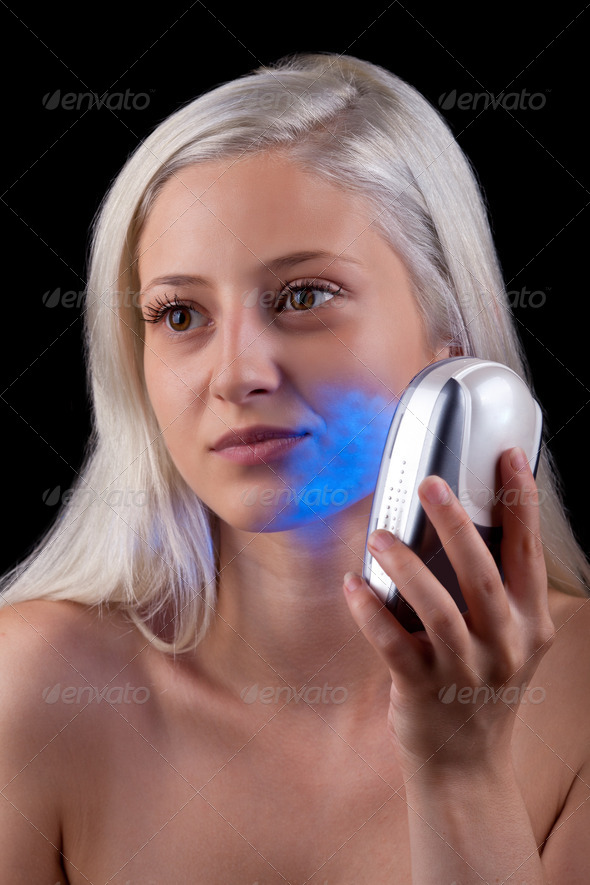 Young woman getting photo-therapy treatment with blue light - Stock Photo - Images