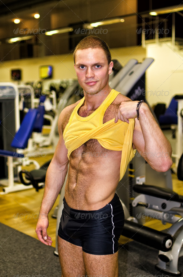Handsome bodybuilder showing his body in a gym - Stock Photo - Images