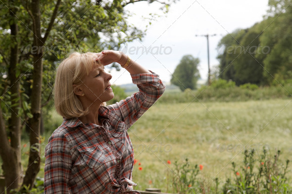 A mature woman looking over the fields - Stock Photo - Images