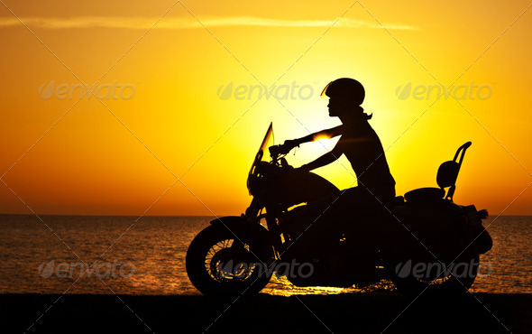 Woman biker over sunset - Stock Photo - Images