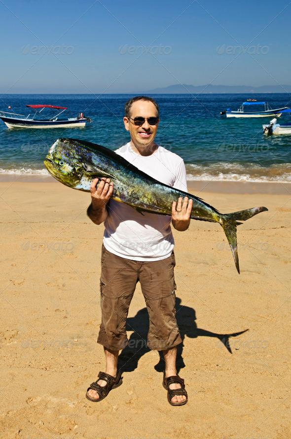 Tourist Holding Big Fish On Beach - Stock Photo - Images