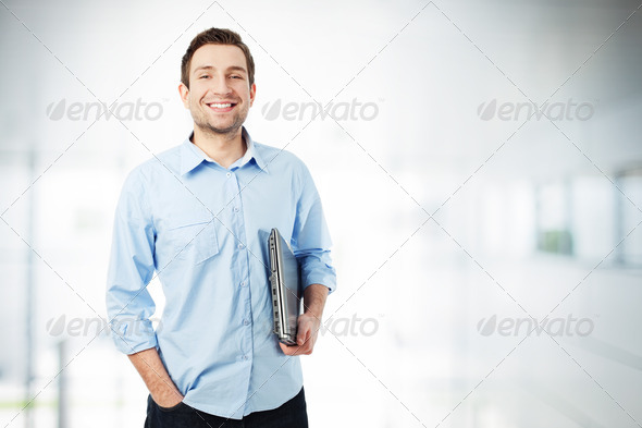 Happy businessman with laptop smiling - Stock Photo - Images
