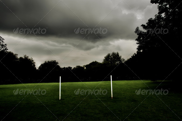 Sunlit Goalposts against Dark Trees and Clouds - Stock Photo - Images