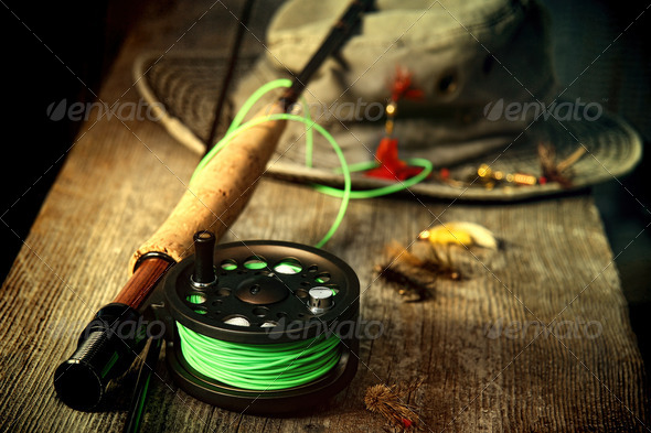 Fly fishing equipment with old hat on bench - Stock Photo - Images