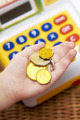 Child's Hand Holding Pretend Coins Next To Toy Cash Register - PhotoDune Item for Sale