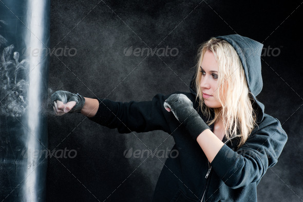 Blond boxing woman in black punching bag - Stock Photo - Images