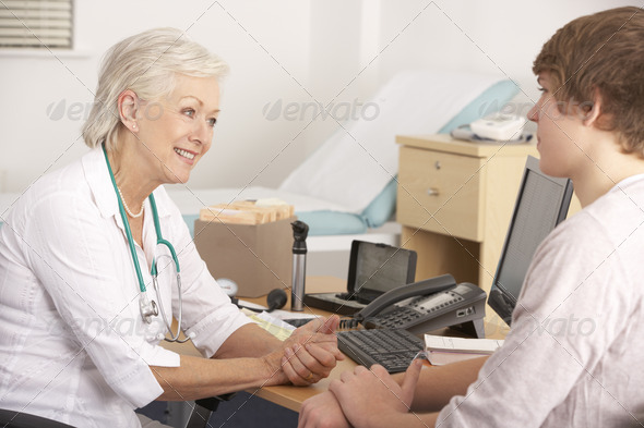 British GP talking to young male patient - Stock Photo - Images