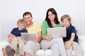 Happy family using laptop at home - PhotoDune Item for Sale