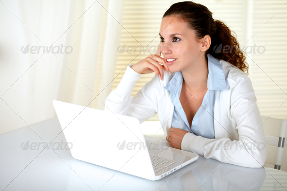 Pensive young woman in front of her laptop - Stock Photo - Images