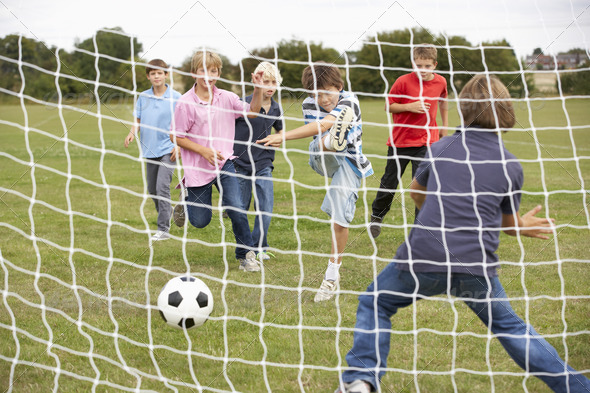 Boys playing soccer in park - Stock Photo - Images
