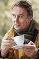 Man In Outdoor Café With Hot Drink  Wearing Winter Clothes - PhotoDune Item for Sale