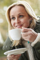 Woman In Outdoor Café With Hot Drink  Wearing Winter Clothes - PhotoDune Item for Sale