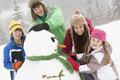 Group Of Children Building Snowman On Ski Holiday In Mountains - PhotoDune Item for Sale