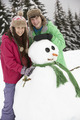 Two Teenagers Building Snowman On Ski Holiday In Mountains - PhotoDune Item for Sale