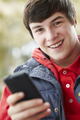 Teenage Boy Texting On Smartphone Wearing Winter Clothes - PhotoDune Item for Sale