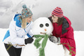 Two Female Friends Building Snowman On Ski Holiday In Mountains - PhotoDune Item for Sale
