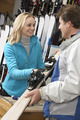 Female Sales Assistant Handing Skis To Customer In Hire Shop - PhotoDune Item for Sale