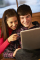 Teenage Couple Relaxing On Sofa With Laptop - PhotoDune Item for Sale