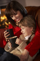 Mother And Daughter Relaxing With Hot Drink Watching TV By Cosy Log Fire - PhotoDune Item for Sale