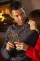 Middle Aged Couple Sitting Sofa By Cosy Log Fire With Glass Of Champagne - PhotoDune Item for Sale