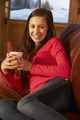 Teenage Girl Relaxing On Sofa With Hot Drink - PhotoDune Item for Sale