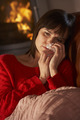 Sick Woman With Cold Resting On Sofa By Cosy Log Fire - PhotoDune Item for Sale