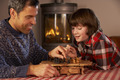 Father And Son Playing Chess By Cosy Log Fire - PhotoDune Item for Sale