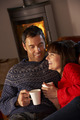 Middle Aged Couple Sitting On Sofa By Cosy Log Fire With Hot Drink - PhotoDune Item for Sale