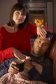 Wife Nursing Sick Husband With Cold Resting On Sofa By Cosy Log Fire - PhotoDune Item for Sale