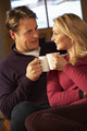 Middle Aged Couple Sitting On Sofa With Hot Drinks - PhotoDune Item for Sale