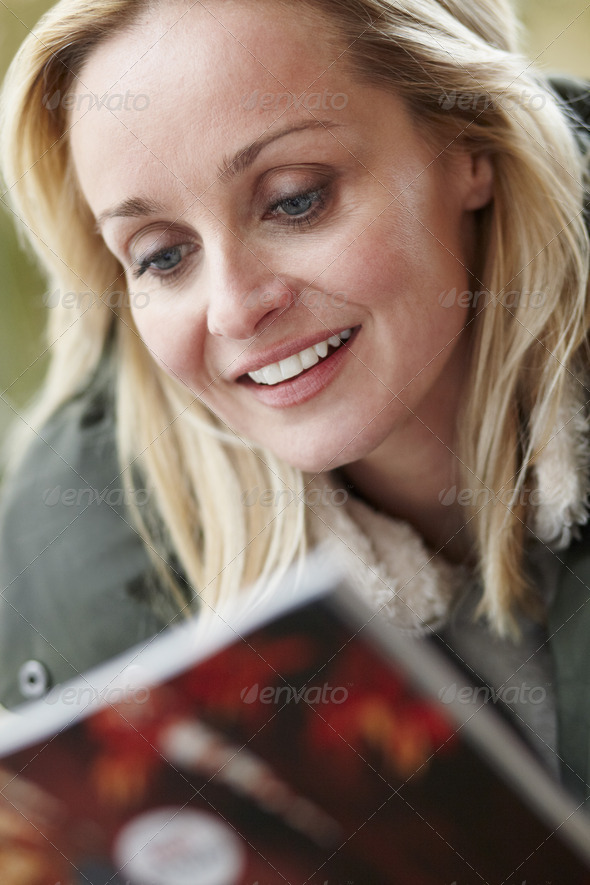 Outdoor Portrait Of Woman Wearing Winter Clothes Reading Magazine - Stock Photo - Images