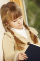 Young Girl Sitting On Wooden Seat Reading Book - PhotoDune Item for Sale