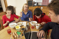 Teenage Family Using Gadgets Whilst Eating Breakfast Together In Kitchen - PhotoDune Item for Sale