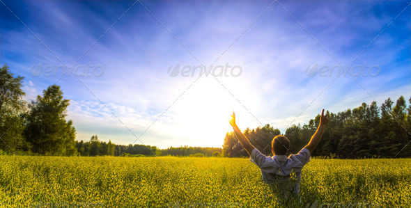 Man praising in field - Stock Photo - Images
