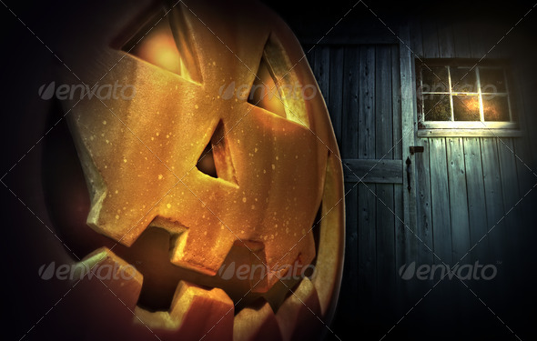 Glowing pumpkin at night in front of barn door - Stock Photo - Images