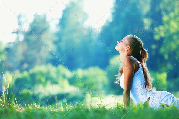 Young woman doing yoga exercise in green park - Stock Photo - Images