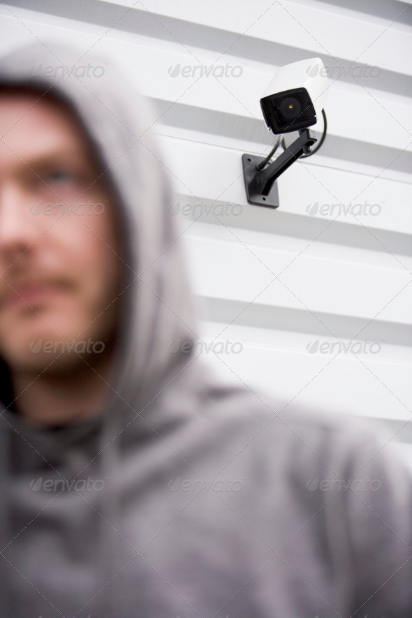 PhotoDune Surveillance Camera And Young Man In Hooded Sweatshirt 325894