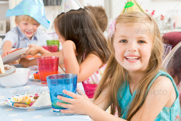 Young girl at party sitting at table with food smiling - Stock Photo - Images