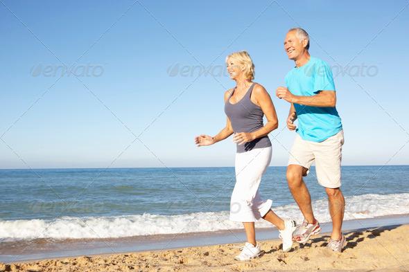 PhotoDune Senior Couple In Fitness Clothing Running Along Beach 326377