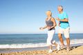 Senior Couple In Fitness Clothing Running Along Beach - PhotoDune Item for Sale