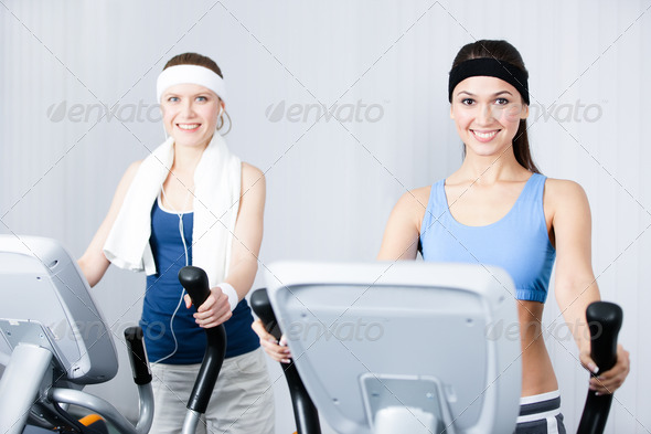Two women training on training apparatus in gym - Stock Photo - Images