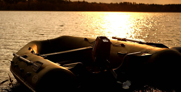 Rubber Motorboat On Lake Coast At Sunset