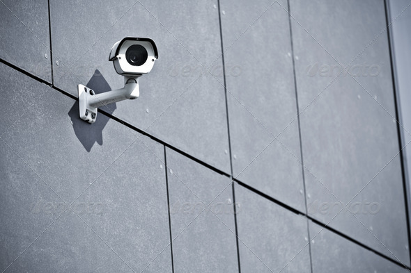 Security camera on office building wall - Stock Photo ...