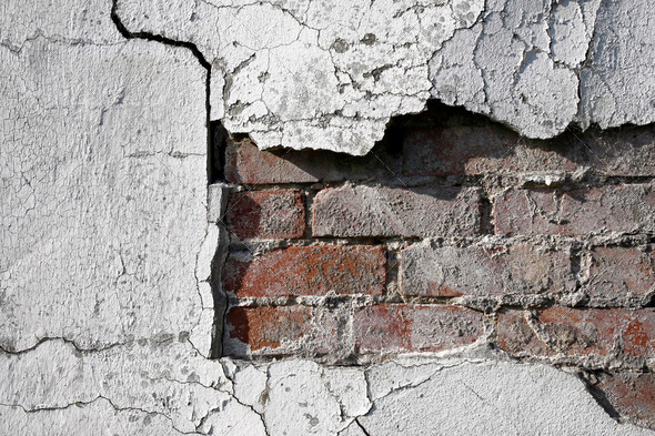Cracked wall with bricks underneath - Stock Photo - Images