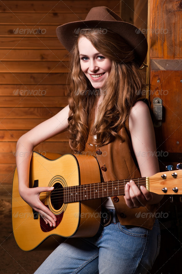 Beautiful caucasian cowgirl with guitar - Stock Photo - Images