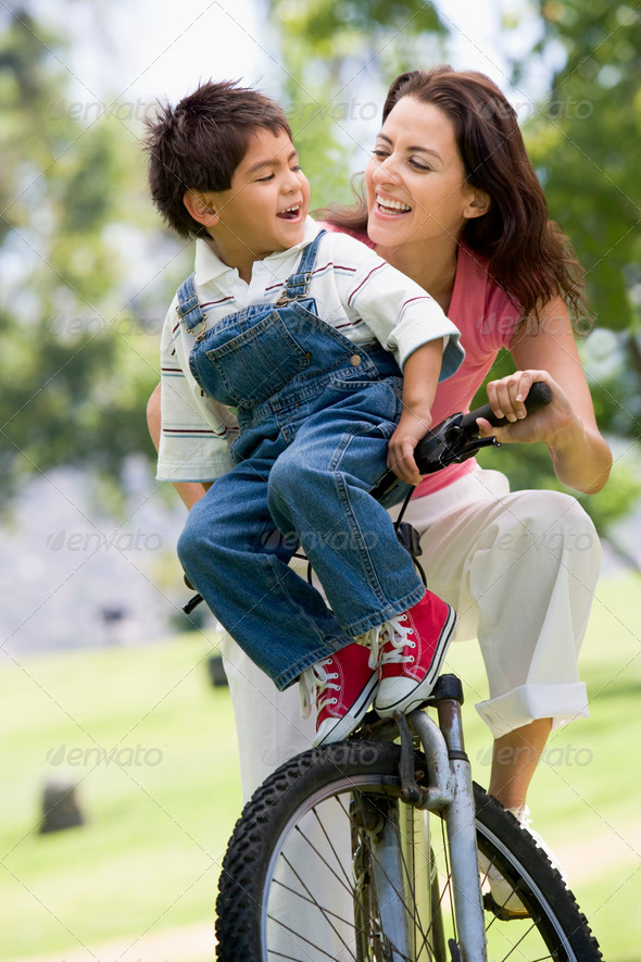 Woman and young boy on a bike outdoors smiling - Stock Photo - Images