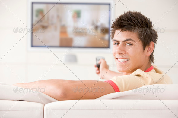 Man in living room watching television smiling - Stock Photo - Images