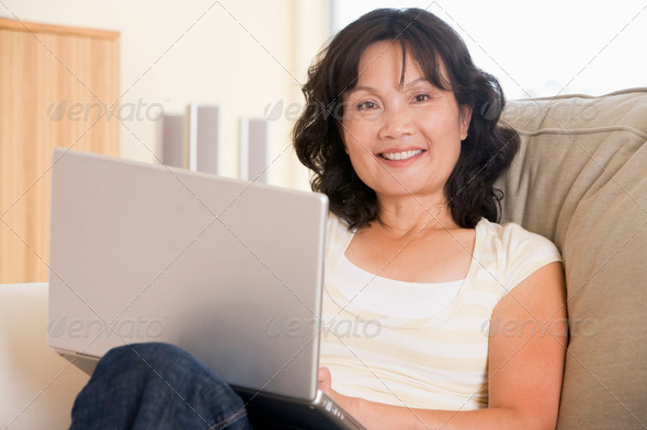 Woman in living room using laptop and smiling - Stock Photo - Images
